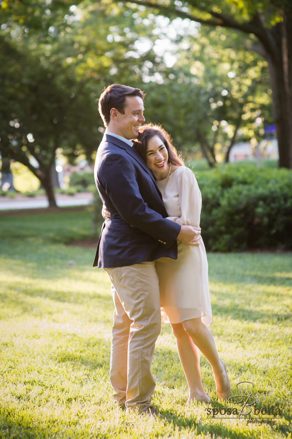Engaged couple happily embraces underneath the warm sunshine.