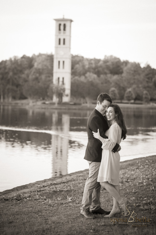 Engaged couple happily embraces with the Furman clock tower in the background.