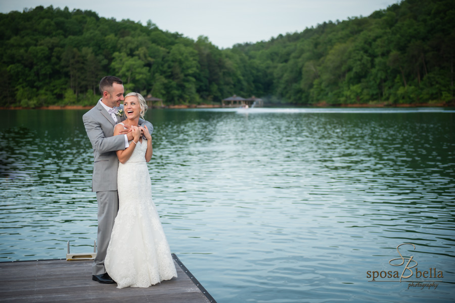 A happy couple hugs and laughs standing on a dock with Lake Keowee in the background.