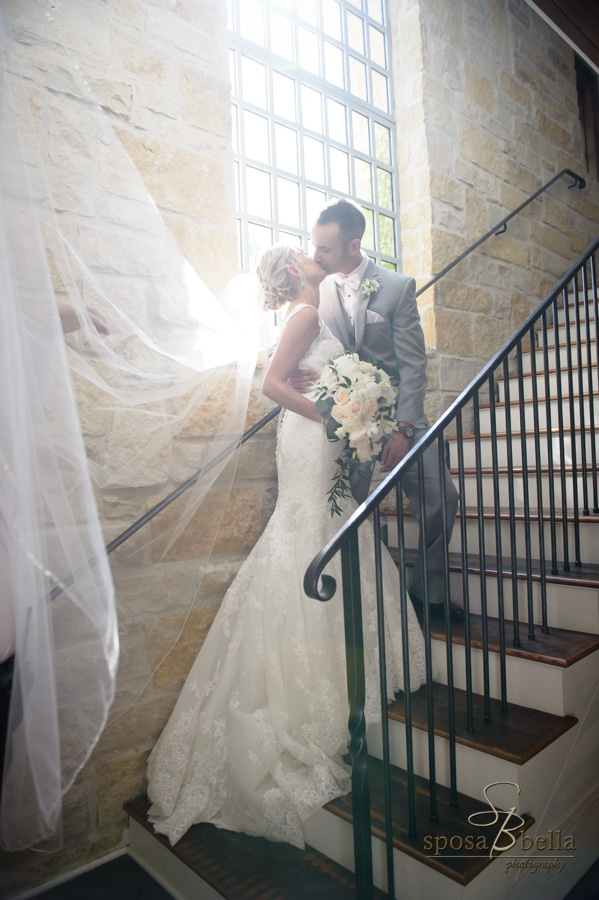 Beautiful back-lit photo of a bride and groom on a staircase.