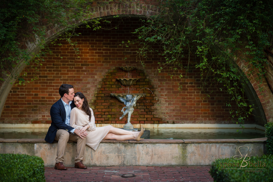 Soon-to-be husband gently kisses his fiance as the snuggle in front of a fountain.