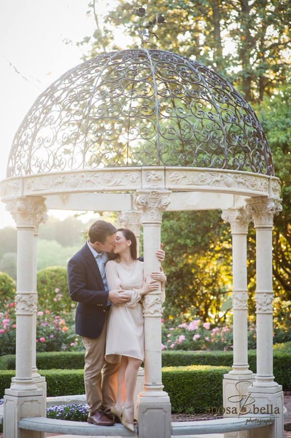 Engaged couple shares a kiss underneath a wrought iron pavilion in the scenic Furman Rose Garden.