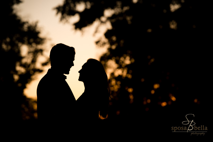 Engaged couple smiles and shares a gaze as their silhouette is framed by the sunset.