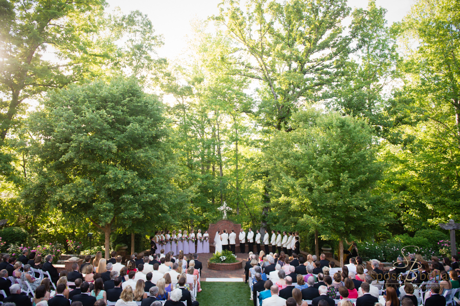 An aerial shot of the entire wedding ceremony with the sun peeking through the treetops.