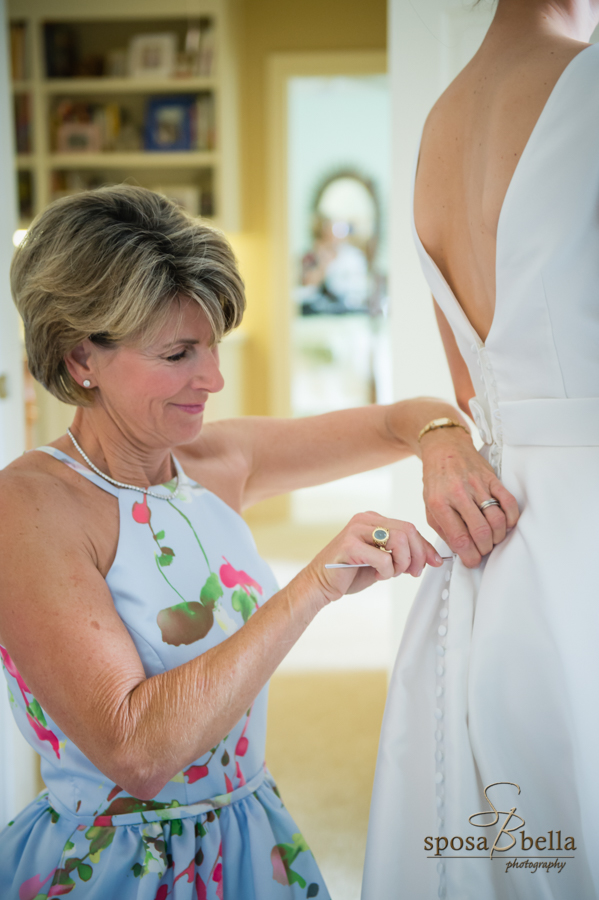 The mother of the bride helping the bride button up the back of her dress.
