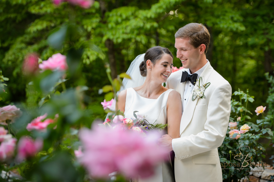 The bride and groom snuggle among roses in the garden shortly after the ceremony.