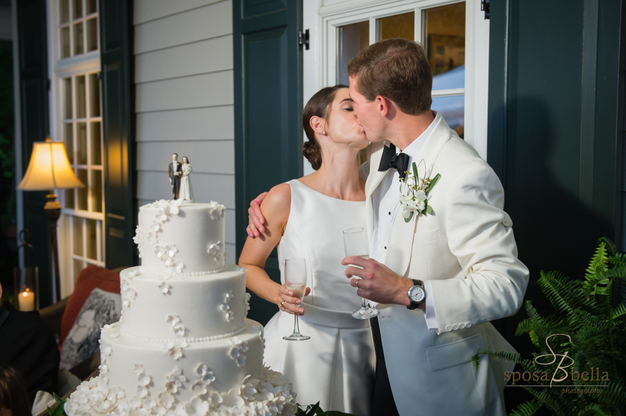 The bride and groom kiss after their toast before cutting the wedding cake.
