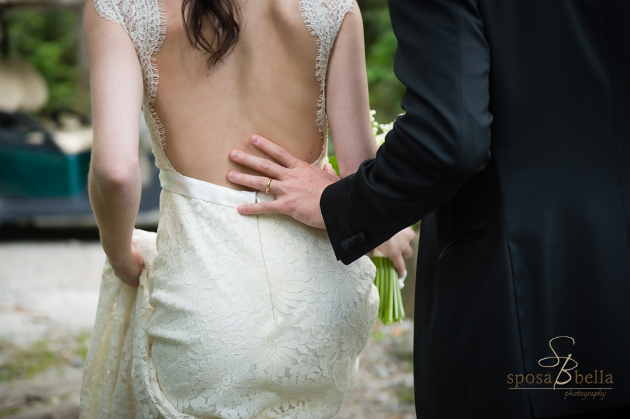 Detail shot of groom's hand on the bride's back featuring his new ring.