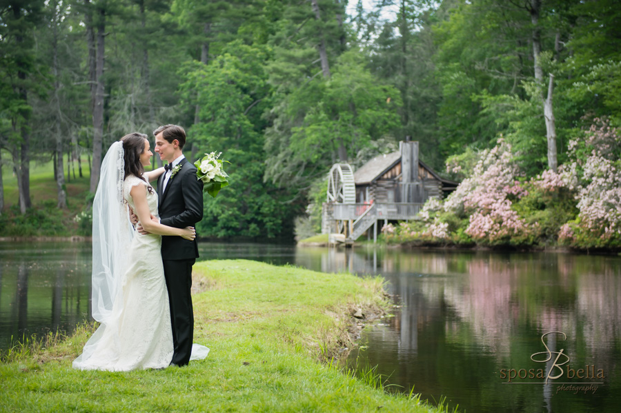Bride and groom gaze sweetly at one another with a historic mill and pond in the background.