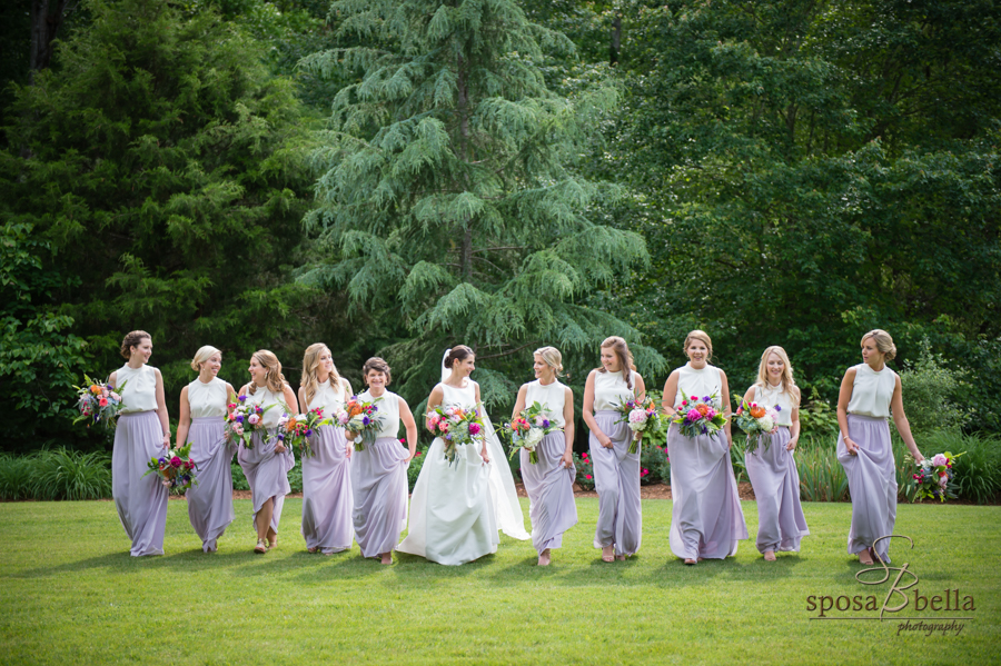 The bride and bridesmaids share a laugh with towering evergreens in the background.