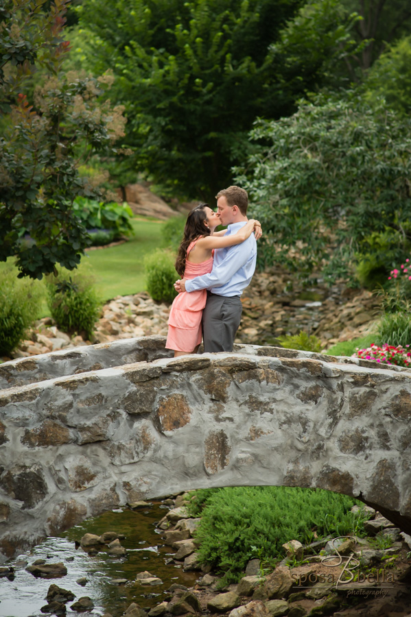 Fiance's kiss on a cobblestone bridge.