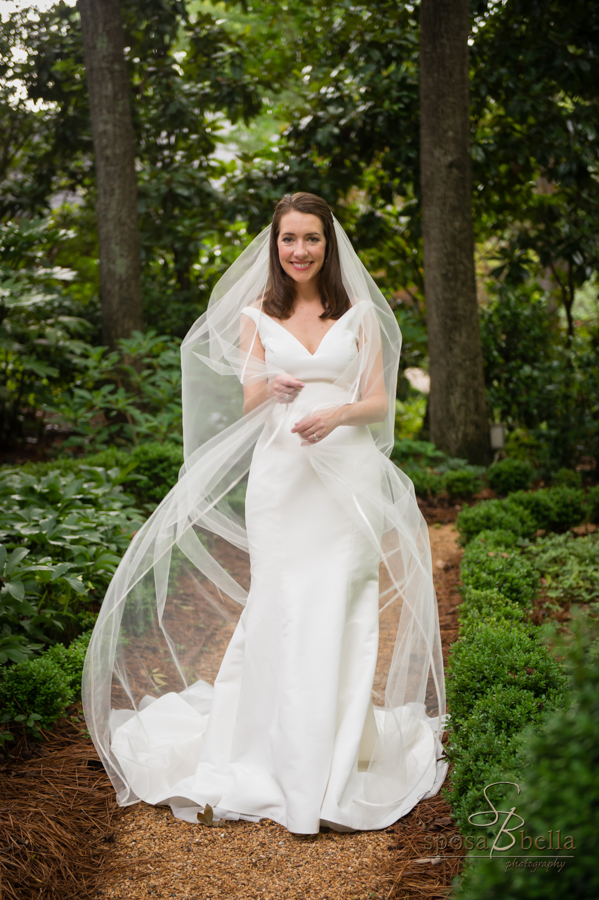 Bride carefully wraps her veil around herself while standing in a garden.