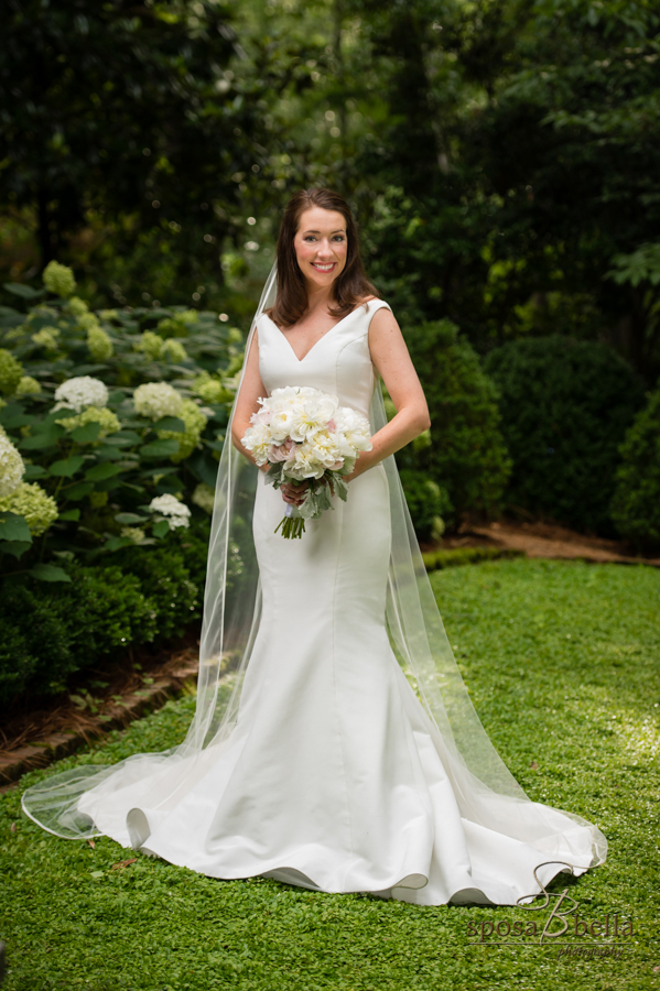 Bride smiles and poses among white hydrangeas matching her bouquet.