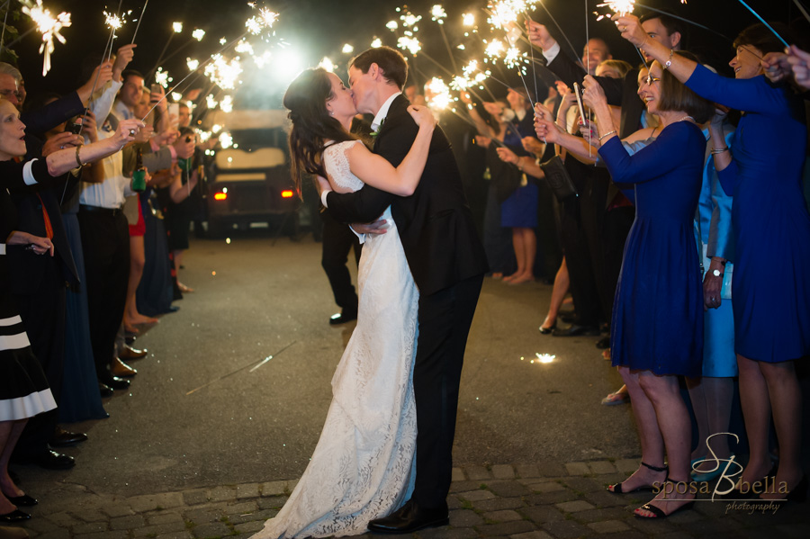 The newlyweds kiss one last time before they leave their reception while surrounded by sparklers.