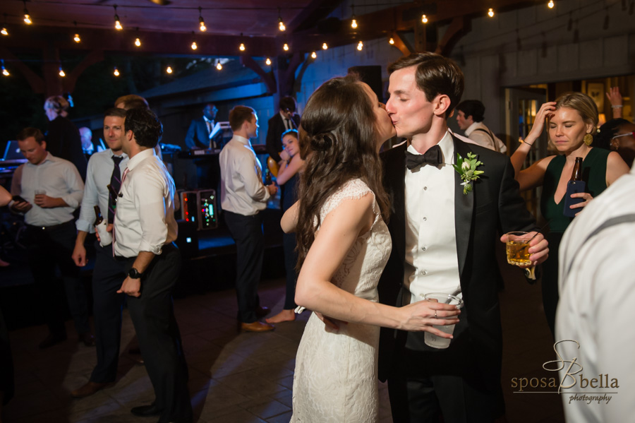 Bride and groom kiss while dancing at their reception.