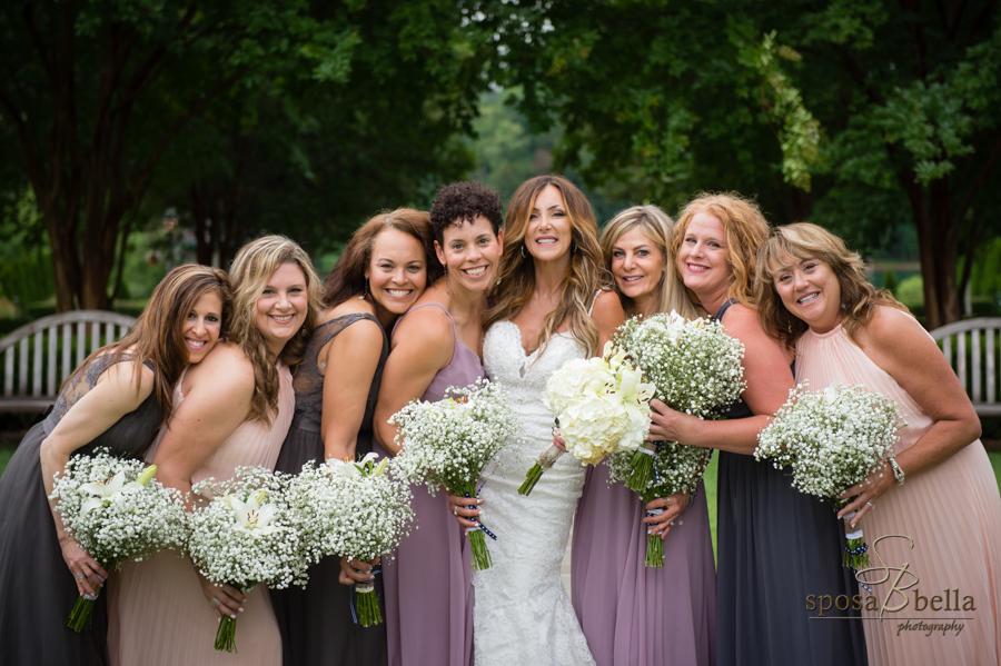 The bride and her bridesmaids all lean in for a group shot.