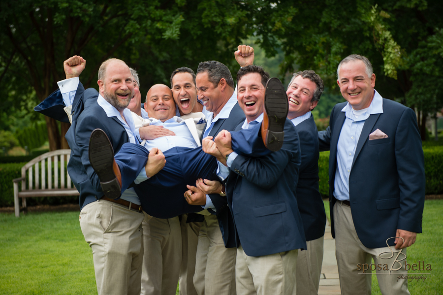 The groomsmen jokingly lift up the groom during their group photo.
