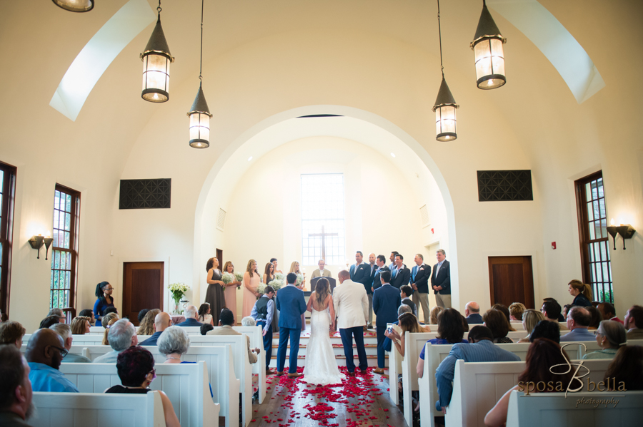 The bride, groom, and their families all stand at the front of the chapel.