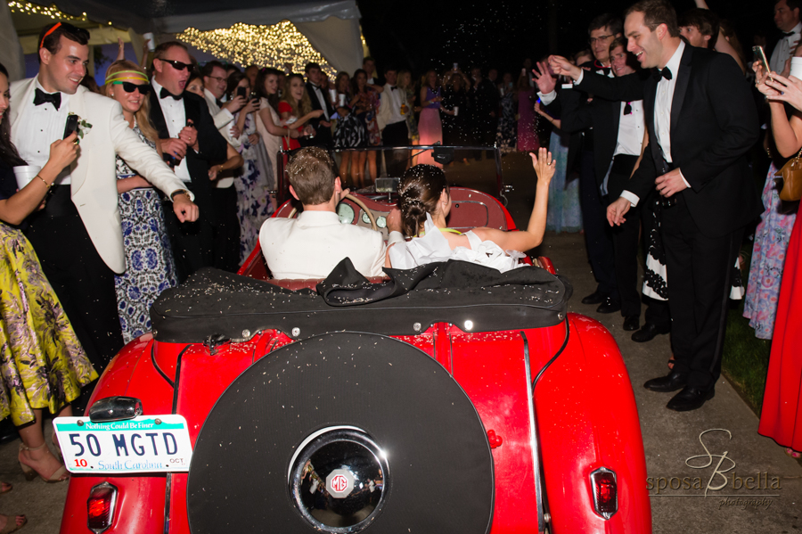 The bride and groom exit the reception in a bright red car.