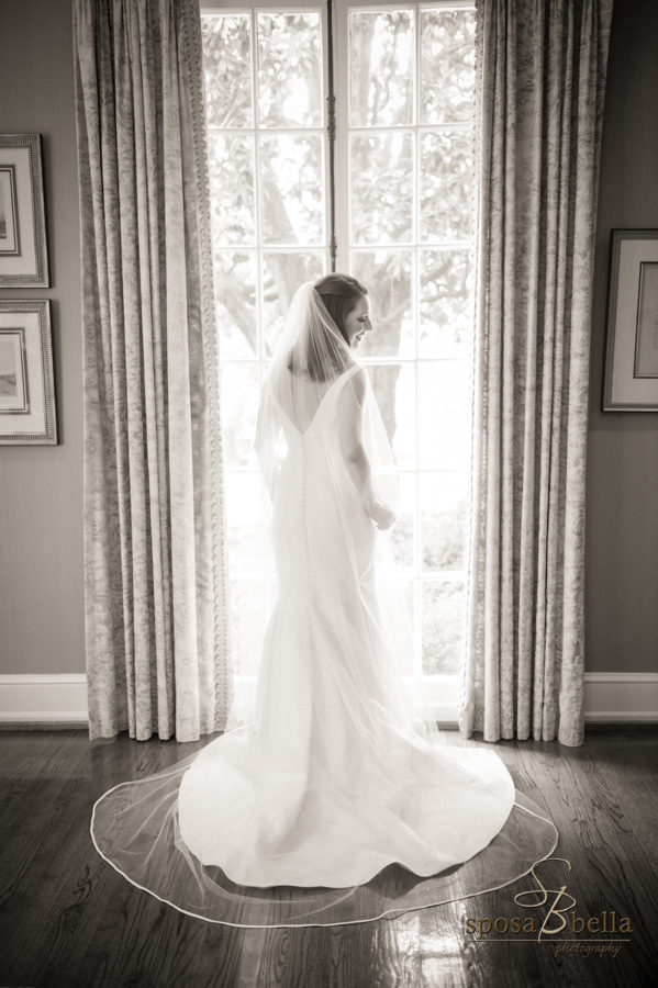 Bride stands at the window of the Poinsett Club.