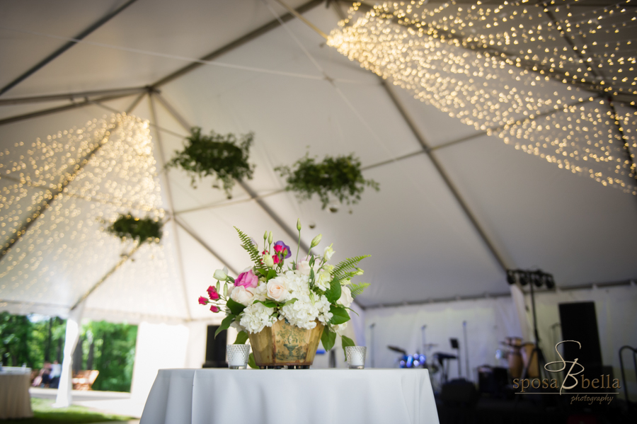 A shot of the flower arrangements at the reception with string lights hanging from the top of the tent in the background.