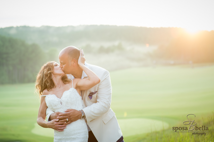 The bride and groom kiss on the beautiful Reserve golf course.