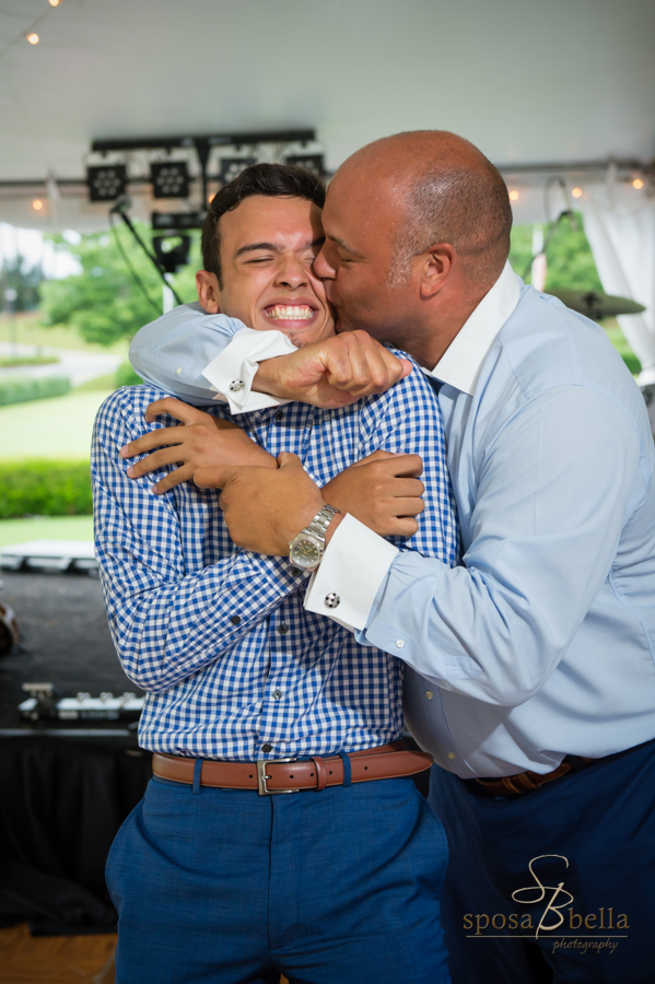 The groom kisses his son on the cheek.