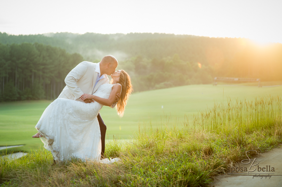 The groom kisses his wife as the sunset shines in the distance.