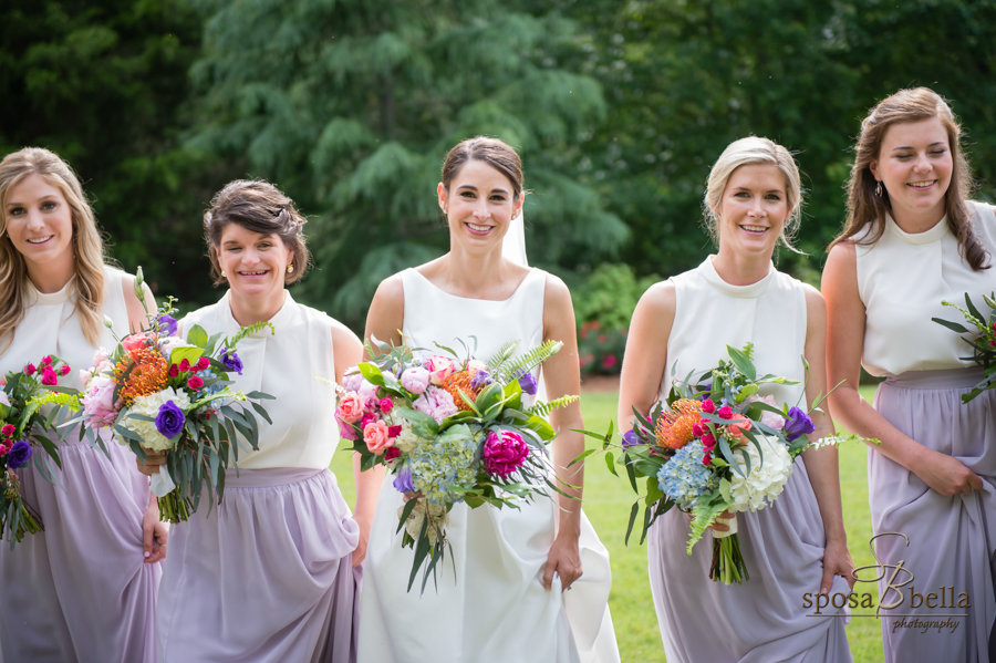 The bride and her bridesmaids all smile as they walk along the grass.
