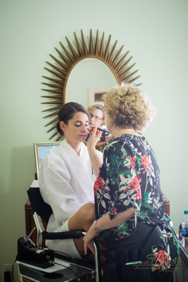 Bride getting her makeup done before her wedding.