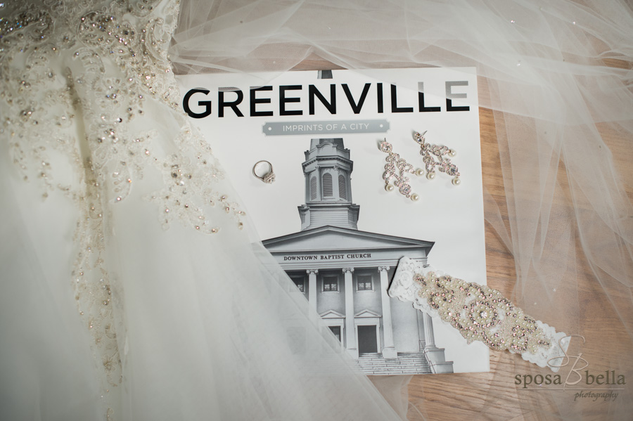 City of Greenville coffee table book with a bride's dress, garter, engagement ring, and earrings laying on it.