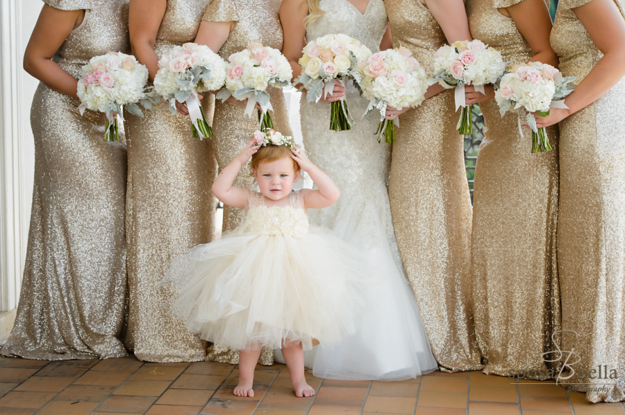 Flower girl in tutu standing in front of Bride and bridesmaids.