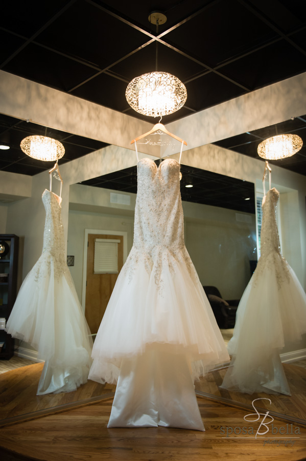 Wedding dress hangs in bride's getting ready room.