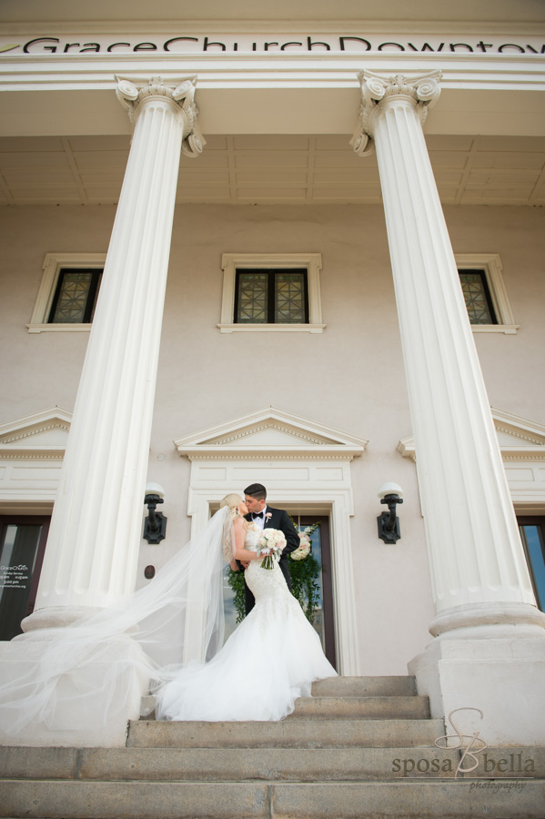 Couple kissing between the gigantic columns outside of Grace Church Downtown.