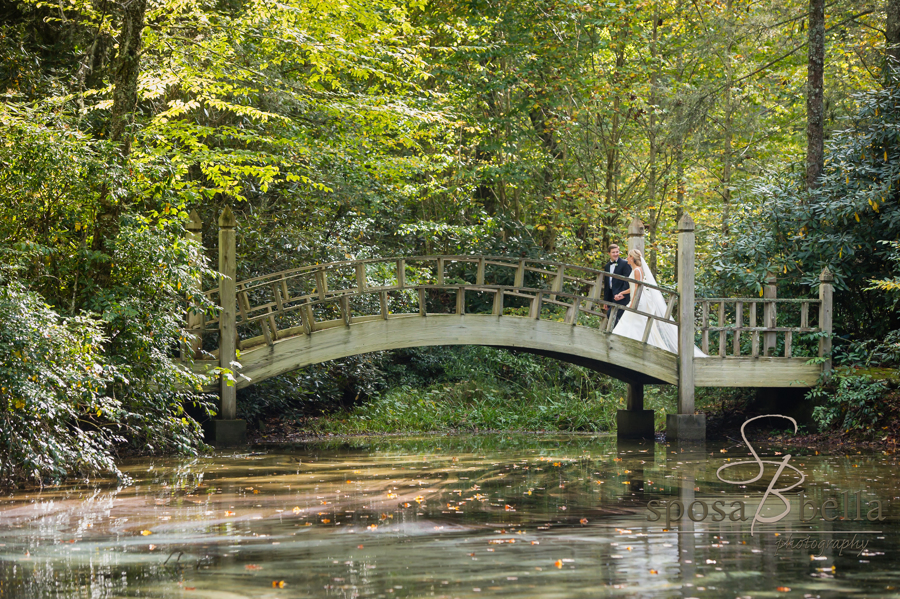 The couple takes advantage of the beautiful mountain scenery for a photo on an old wooden bridge.