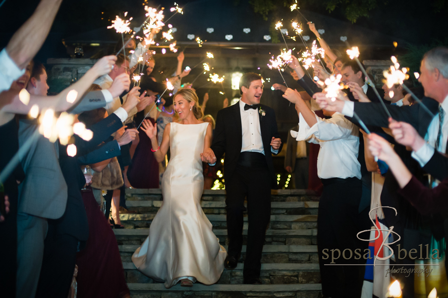 Leland and Charlie wave goodbye to their guests under a shower of sparklers.