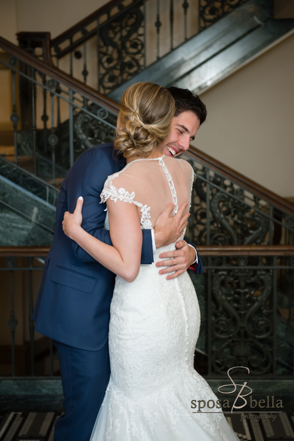 Groom hugs his bride with big smile on his face.