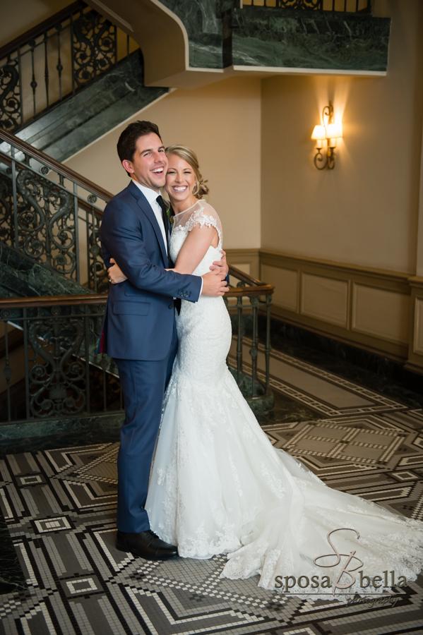 Bride in wedding dress hugs her husband.