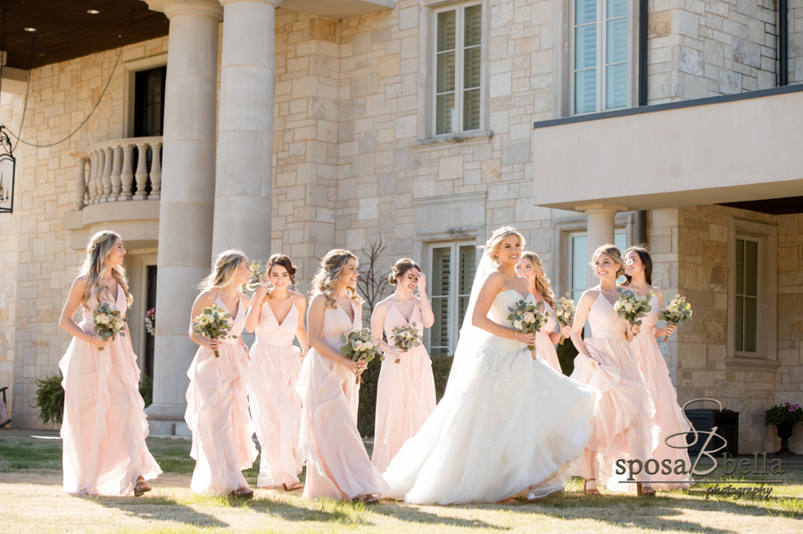 Bride walks through grass surrounded by bridal party.