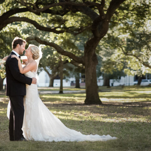 A bride hugs her groom under a canopy of back lit oak trees.